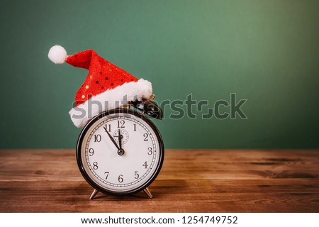 Alarm clock with santa hat on wooden table #1254749752