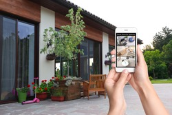 Alarm system. Woman monitoring modern CCTV cameras on smartphone at backyard, closeup