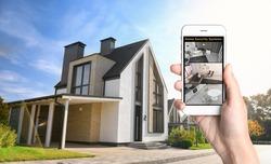 Alarm system. Woman monitoring modern CCTV cameras on smartphone near her house, closeup