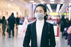 Alarmed female traveler wears medical mask to protect against coronavirus, afraid of infection, in shopping center. Deadly coronavirus in China 2019 2020 2019-nov. Free space for text or advertising.