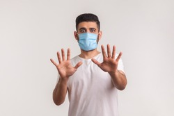 Alarming scared panicking man in hygienic mask gesturing stop, afraid of coronavirus infection, respiratory illnesses such as flu, 2019-nCoV, Covid-19, ebola. indoor shot isolated on white background