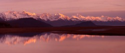 Alaska Coastal Mountain Range Reflection - The coastal mountain range across the Lynn Canal with alpenglow at sunset is reflected in a pool of water in the Chillkat Valley. Haines, Alaska.