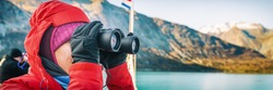 Alaska cruise travel tourist whale watching on boat shore excursion ride at Glacier Bay landscape. Woman looking at view binoculars on cruise ship. Panoramic banner portrait.