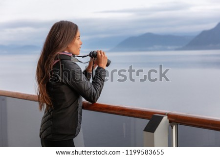 Alaska cruise woman on whale watching boat excursion tour looking at wildlife with binoculars. Tourist at inside passage Glacier Bay destination on travel ship vacation enjoying scenic cruising.