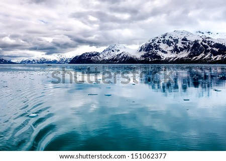 Alaska wilderness landscape at Glacier Bay National Park, featuring floating ice, dramatic clouds and snowy mountains with reflections in the bay's blue water.