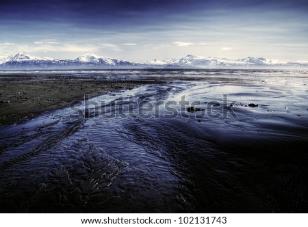 Alaskan beach near Homer at low tide with water flowing to the sea and snow covered mountains in the background.