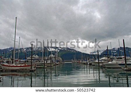 Alaskan boat and fishing harbor in Seward, Alaska with mountains and glacier