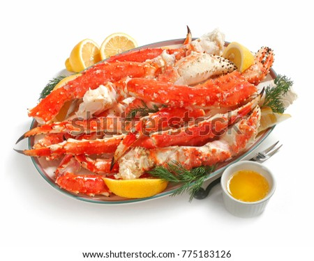 Alaskan King Crab legs on platter, served with lemon and butter, on white background #775183126
