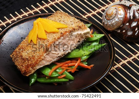 Alaskan Salmon with sesame crust, green split peas and mango on top.