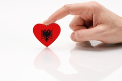 Albania flag. Love and respect Albania. A man's hand holds a heart in the shape of the flag of Albania on a white glass surface. The concept of Albanian patriotism and pride.