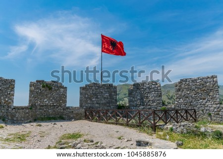 Albanian red flag with a black double-headed eagle towers above the fortress of Rozafa. #1045885876