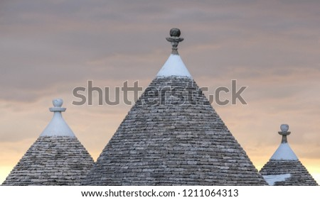 Alberobello Italy. Conical roofs of traditional dry stone trulli houses in Alberobello, Puglia. Photographed in early morning with red sky in background.