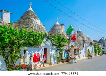 ALBEROBELLO, ITALY, JUNE 21, 2014: Tourists are enjoying sunny day among trulli houses in Alberobello, Italy. #779118574