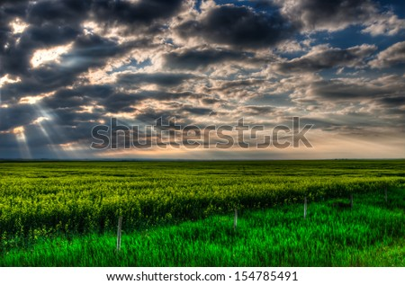 Alberta farmland under stormy skies at sunset