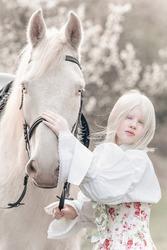 albino girl with a horse albino in a blooming garden
