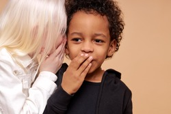 albino girl with pale skin and white hair color tells a secret in the ear of multiracial africanamerican boy. cute boy with black skin attentively listen to secret. isolated