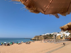 Albufeira Algarve beach from under parasol, July 2020. Socially distanced beach goers during COVID