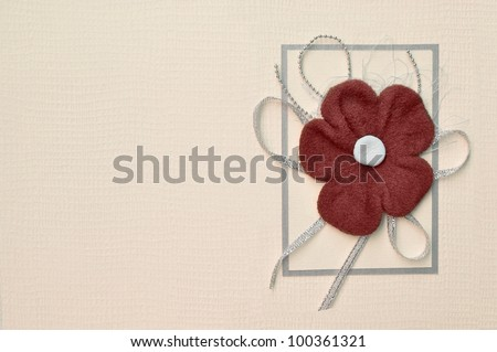 Album book cover background. Handmade paper invitation or greeting card decorated with red suede flower design and a bow.