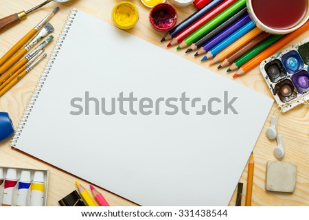 Album pages and paints, pencils,oil, brush on a wooden background  Stock photo ©