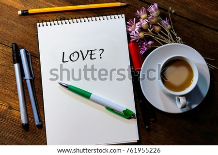 album, pens and pencils on a wooden table. a cup of coffee with milk. inscription - love. #761955226