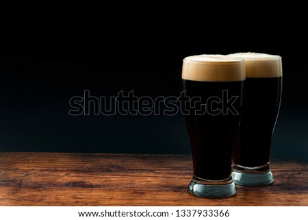 Alcohol abuse, bitter refreshing alcoholic beverage and dry stout concept theme with frothy glass pints of dark beer on wood table isolated on black background with copyspace in bar or pub setting Stock photo ©