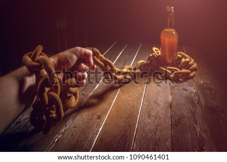 Alcohol addiction concept. Beer addiction. Chains and lock. Beer in the chains.