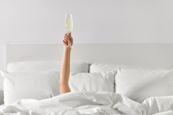 alcohol, celebration and morning concept - hand of young woman lying in bed with champagne glass