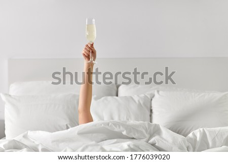 alcohol, celebration and morning concept - hand of young woman lying in bed with champagne glass Сток-фото ©