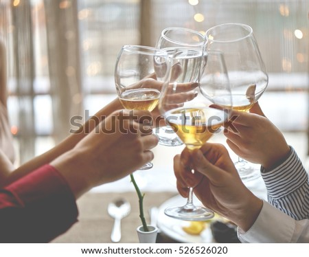 Alcohol cheers clinking glasses of champagne in hands on bright lights background