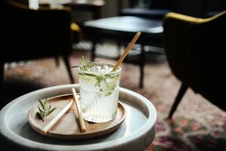 Alcohol cocktail drink with bamboo straws in bar interior on the table
