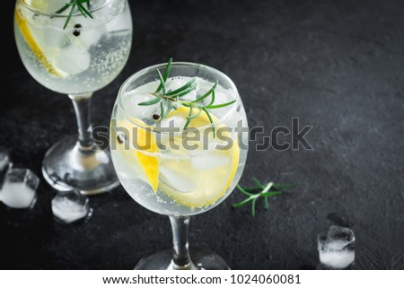Alcohol drink (gin tonic cocktail) with lemon, rosemary and ice on rustic black stone table, copy space, top view. Iced drink with lemon. Foto stock ©