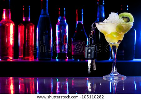 Alcohol drink in cocktail glass and car keys hanging from it