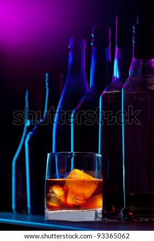 Alcohol drink with ice and silhouette of the different bottles on dark background