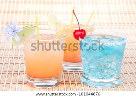 Alcohol margarita cocktails, long island Iced tea, blue lagoon with lime and summer flower in short cocktail glasses isolated on a white background