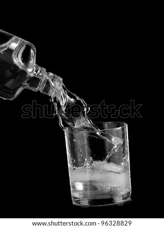 Alcohol pouring into a glass with ice