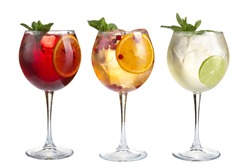 Alcoholic and non-alcoholic refreshing cocktails with mint, fruits and berries on a white background. Three cocktails in glass glasses on a long leg. Isolated.