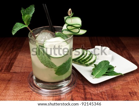 alcoholic beverage on a bar top with cucumber slices, mint and sugar cubes on a plate