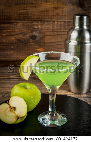 Alcoholic cocktail - Appletini. martini, margarita with apple. Decorated with slice of green apple, with a shaker on a black slate on a wooden table, copy space, vertical #601424177