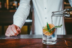 Alcoholic cocktail in bar, Bartender making gin cocktail with garnishes