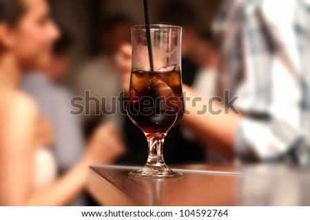 Alcoholic cocktail on bar with happy people background