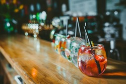 Alcoholic cocktail row on bar table, colorful party drinks