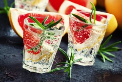Alcoholic cocktail with grapefruit, soda, ice, gin and rosemary, dark stone background, selective focus
