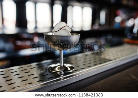 Alcoholic cocktail with ice and coconut in silver glass on bar table. #1138421363