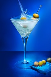 Alcoholic cocktail with olives on blue background