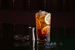 Alcoholic cocktail with rum, orange and ice on black table near ice, jigger and strainer