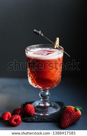 Alcoholic cocktail with strawberry and a piece of ice on a dark background. Close up shot of an alcoholic cocktail. Photography of Cocktail. Bar. Cocktails. Alcohol. Vodka. Party. Cocktail in the bar