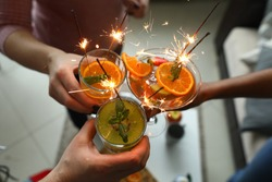 Alcoholic cocktails with fruit pieces, mint and sparklers close up top view. Three people hold glasses and clink glasses.