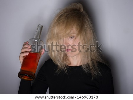 Alcoholic disease concept woman with whiskey bottle with shadows