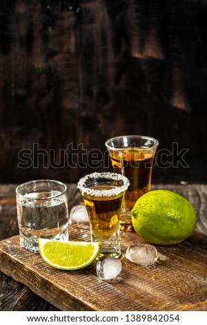 Alcoholic drink concept. Mexican tequila with lime and salt on rustic wood background. space for text. concept luxury drink.