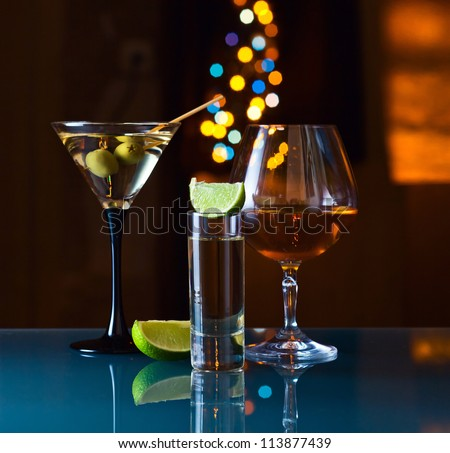Alcoholic drinks in a bar on a glass table.